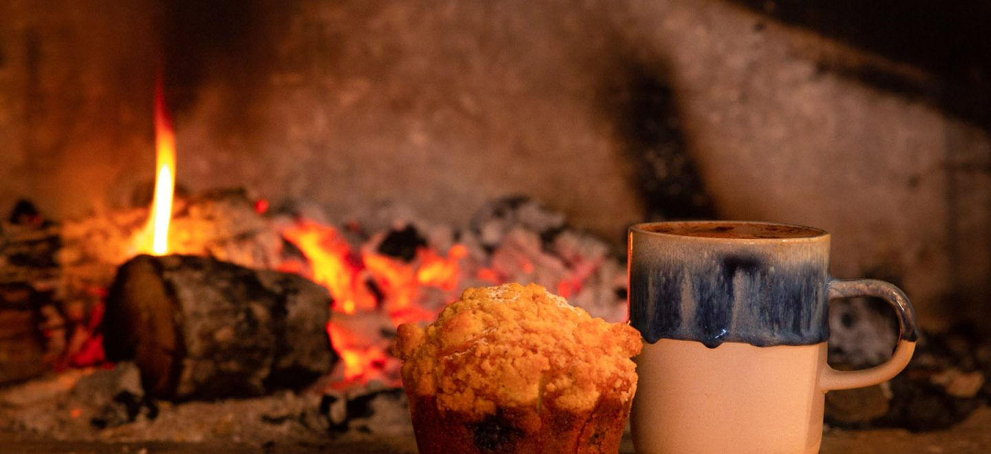 Photograph of a fireplace with a mug and a muffin