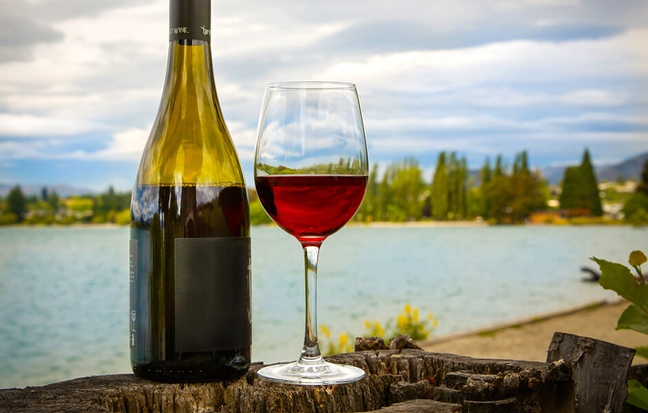 A photograph of a glass of red wine against Lake Wanaka